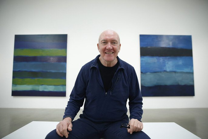 "Artist Sean Scully poses with his works ""Landline BrŸke 5.14"" (L) and ""Landline Blue Blue"" at the Timothy Taylor Gallery in London November 20, 2014. REUTERS/Luke MacGregor (BRITAIN - Tags: ENTERTAINMENT SOCIETY)"